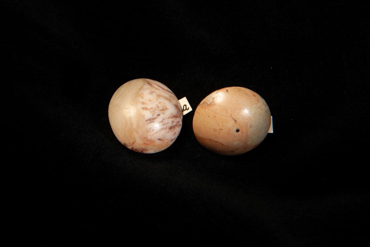 En enkel knapp av slipad ochpolerad brunbeige och vit agat. Fäste i vitmetall. Jämför med JM.19983:b.