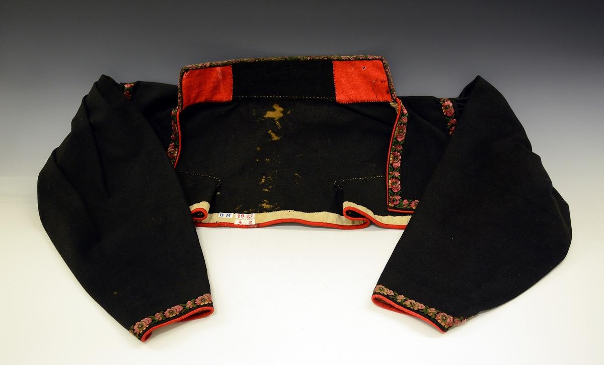 Kvinnetrøye av svart klede, kanta med kjøpeborder i mønster av raudt og grønt på svart botn. Høg krage, ope bryst. Fra protokoll.