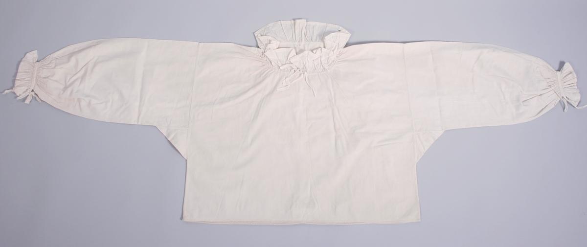 Kort skjorte med sidesømmer. Halsrigningen har løpegang med knyttesnor. Rysjkant i hvit bomull rundt halsrigning og nede på ermene. Ermene er glatt isydde og tett rynket mot rysjkanten som også er tett rynket. Smalt brodert bånd dekker sammensyingen Splitt nederst på ermene som lukkes med knyttebånd. På innsiden av skjorten er det to klistermerker med tekst.