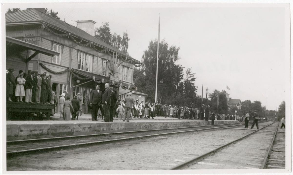 Ljusdal-Hudiksvall 50 år Delsbo station 1938 i väntan på jubileumståget 1888-1938. 28 Augusti 1938. Station anlagd 1888. Tvåvånings stationshus i trä. 1938 utökades stationen med poststation och godsmagasin samt moderniserades expeditionen