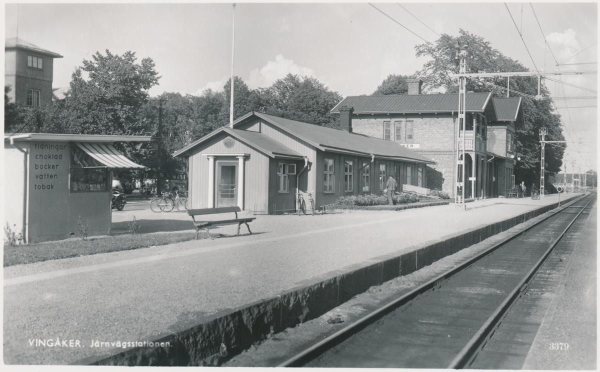 """Stationen anlades 1862. Vingåker station hade stationshus av en lite mer ovanlig modell. Ett imponerande """"kråkslott"""" med många rökhuvar på taket.  Stationshuset har moderniserats under flera omgångar. Stationen upphörde 1996 för all trafik. Järnvägen elektrifierades 1926. Framför stationen på fotot syns postkontoret."""