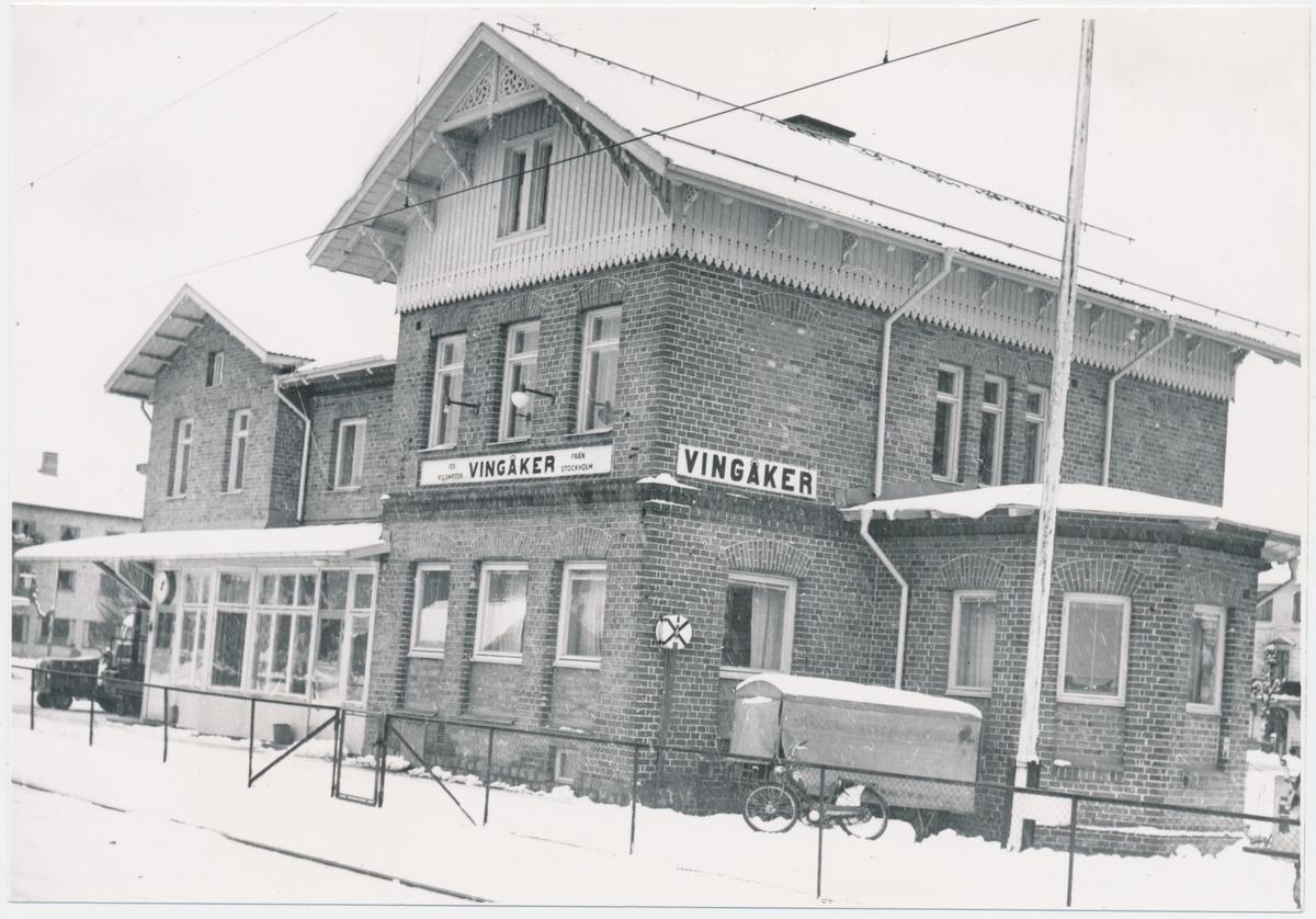 """Stationshus från sydost med modernare fönstren. Stationen anlades 1862. Vingåker station hade stationshus av en lite mer ovanlig modell. Ett imponerande """"kråkslott"""" med många rökhuvar på taket.  Stationshuset har moderniserats under flera omgångar. Stationen upphörde 1996 för all trafik."""