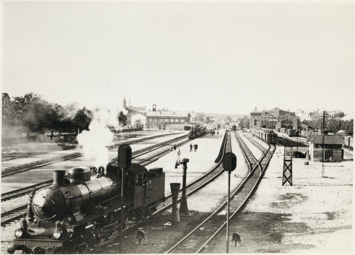 Vy på stationsomåde och bangård med lok, vagnar och resande i bild.
