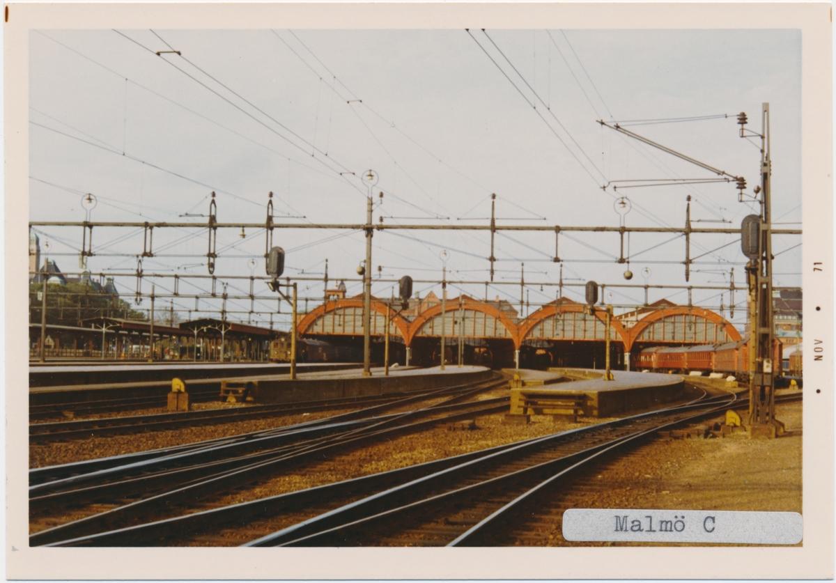 Malmö station 1971. Statens Järnvägar, SJ. Det första stationshuset invigdes 1856, men förstördes delvis i en brand 1866. Vid återuppbyggnaden kunde bara klocktornet bevaras och det andra stationshuset invigdes 1872. Med tiden anslöts fler banor till Malmö och det stora nya stationen med 4 nya spår blev klar 1891.1924 byggdes den nuvarande stationshuset. Banan elektrifierades 1933.