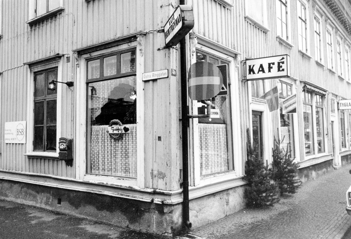 """Gatuvy från hörnet av Kungsgatan-Östra Ringatan som visar Café Hemtrevnads båda sidor. Över ingången sitter en skylt """"Kafé"""". Rörelsen lades ned vid årsskiftet 1980-81."""