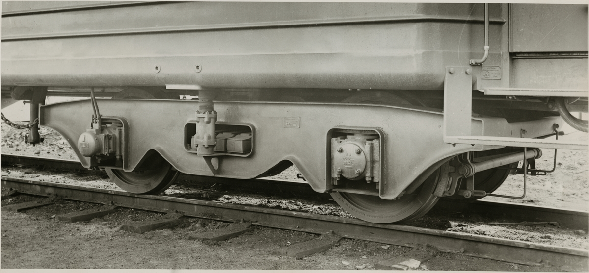 Närbild på boggi monterad på personvagn.