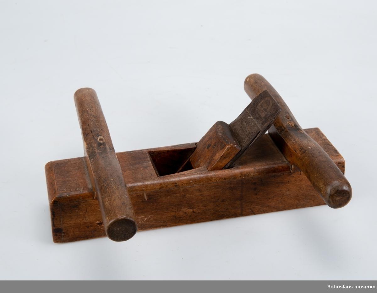 Stocken tillverkad i stycke, fasade, rundade kanter på översidan. Dubbla tvärställda handtag, (för två personer) plan sula och rakt järn, med klaff, bredd på järnet 58 mm. Ritsade linjer, dekoration.  Använd vid hyvling av breda, gröve arbetsstycken, t ex bord till båt. Hyveln komplett, handtagen lite lösa, sulan repad, väl använd. Mörkbetsad ev av bok.  Föremålet ingår i en insamling av eka med segel och åror, båtbyggar-, segelmakeri- och andra verktyg från ett hemman på Stora Askerön i Norums socken, Stenungsunds kommun, Bohuslän. För uppgifter om insamlingen, se UM015587.