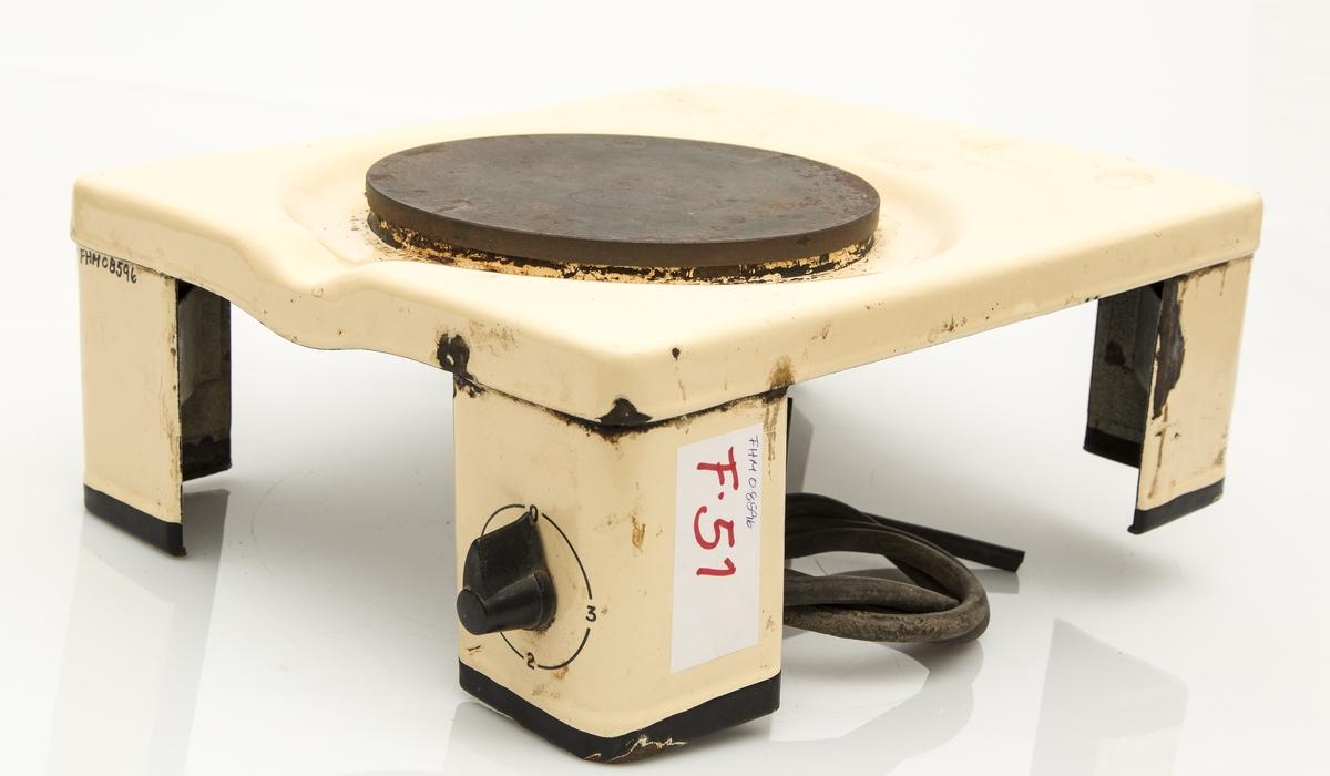 Elektrisk kokeplate i metallstativ med 4 ben. Selve platen litt nedfelt. 3-trinns bryter og ledning