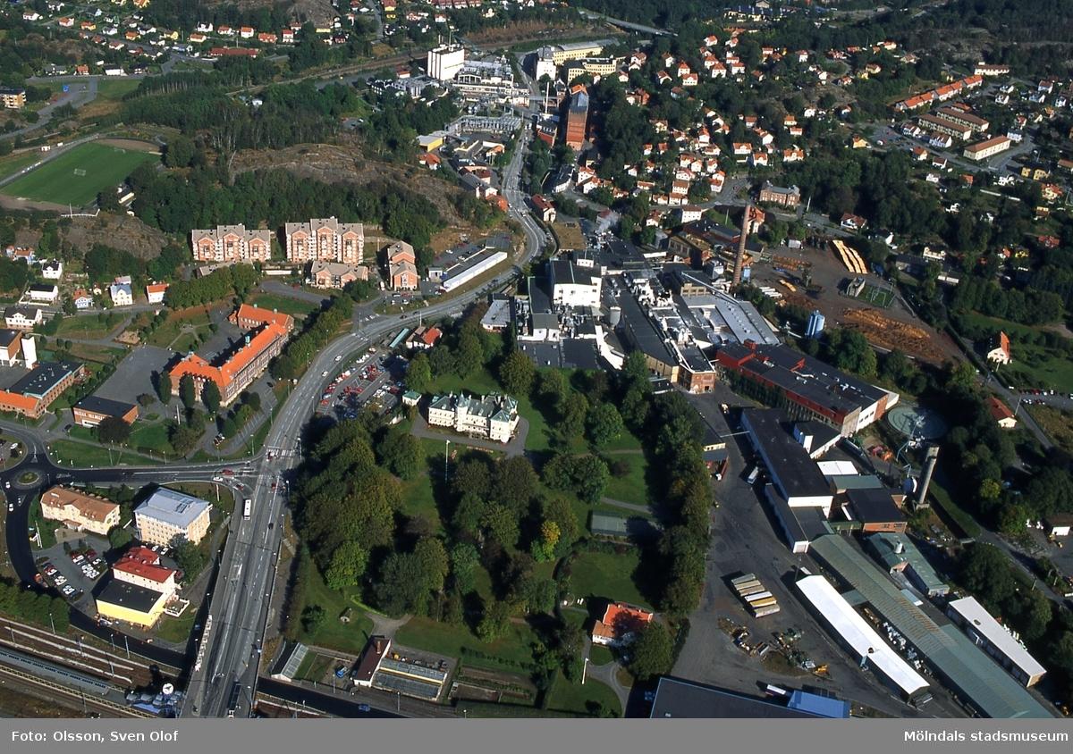 """Flygfotografi över del av Mölndal den 21 september 1995. Närmast ses från vänster Mölndals Bro samt bebyggelse i Trädgården såsom brandstationen, Kvarnbyskolan och bostäder vid Störtfjällsgatan. I mitten Villa Papyrus med dess park. Till höger fabriksbyggnader i Forsåker tillhörande pappersbruket Papyrus. I bakgrunden ses från vänster Kvarnbyvallen, Störtfjället, bebyggelse längs """"Kråkan"""" samt, till höger, bebyggelse i Mölndals Kvarnby. D 21:34."""