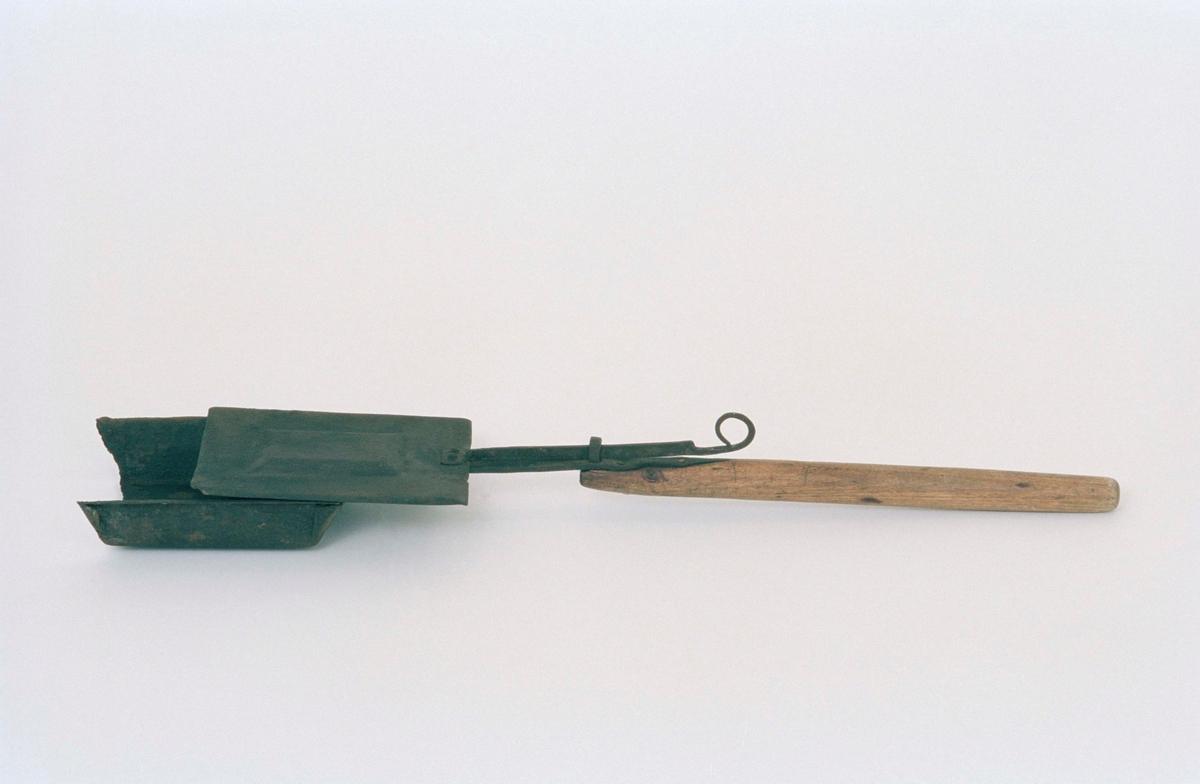 Kaffebrännare av järnplåt med träskaft. Behållaren lådformig med skjutlock; främre gaveln på behållaren saknas 1997.