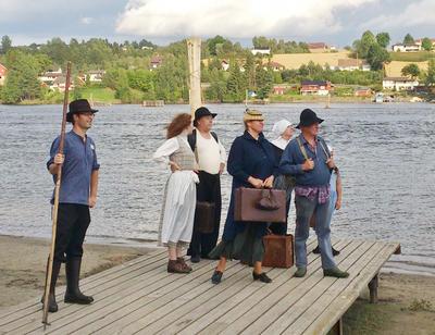 Foto av personer som er utkledd i gamle klær og står på en brygge og ser nedover elva.