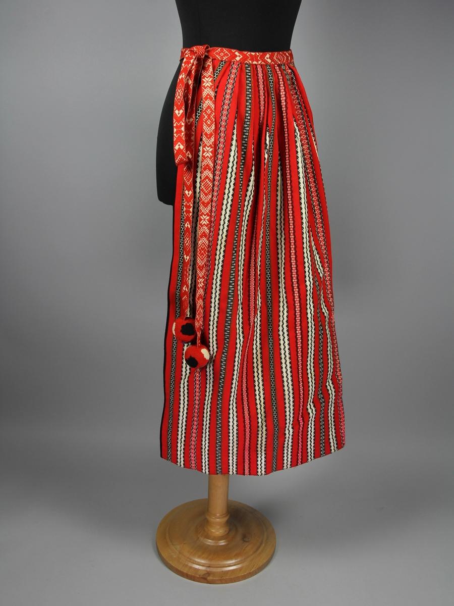 Förkläde av halvylle mönstervävt i ränder med svart, vitt, rött och grönt på röd botten. Upptill är förklädet veckat och sytt mot ett mönstervävt band. Bandet har ett upplockat mönster i rött och grönt mot vit botten. Bandets båda ändar avslutas med en tät prickig garnboll i färgerna gul, grön, rosa röd och vit. Plagget är både handsytt och maskinsytt.