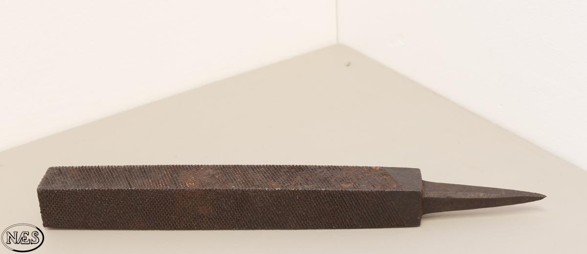 Redskap. En kraftig og grovtannet fil med firkantet tversnitt. Uten skaft. Med mønster på alle fire flatene.