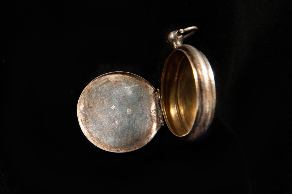 Medaljong i form av en klockboett. Stämplar invändigt på locket: . Släta sidor, en knopp upptill med en oval ring att hänga kedjan i. Invändigt förgylld.