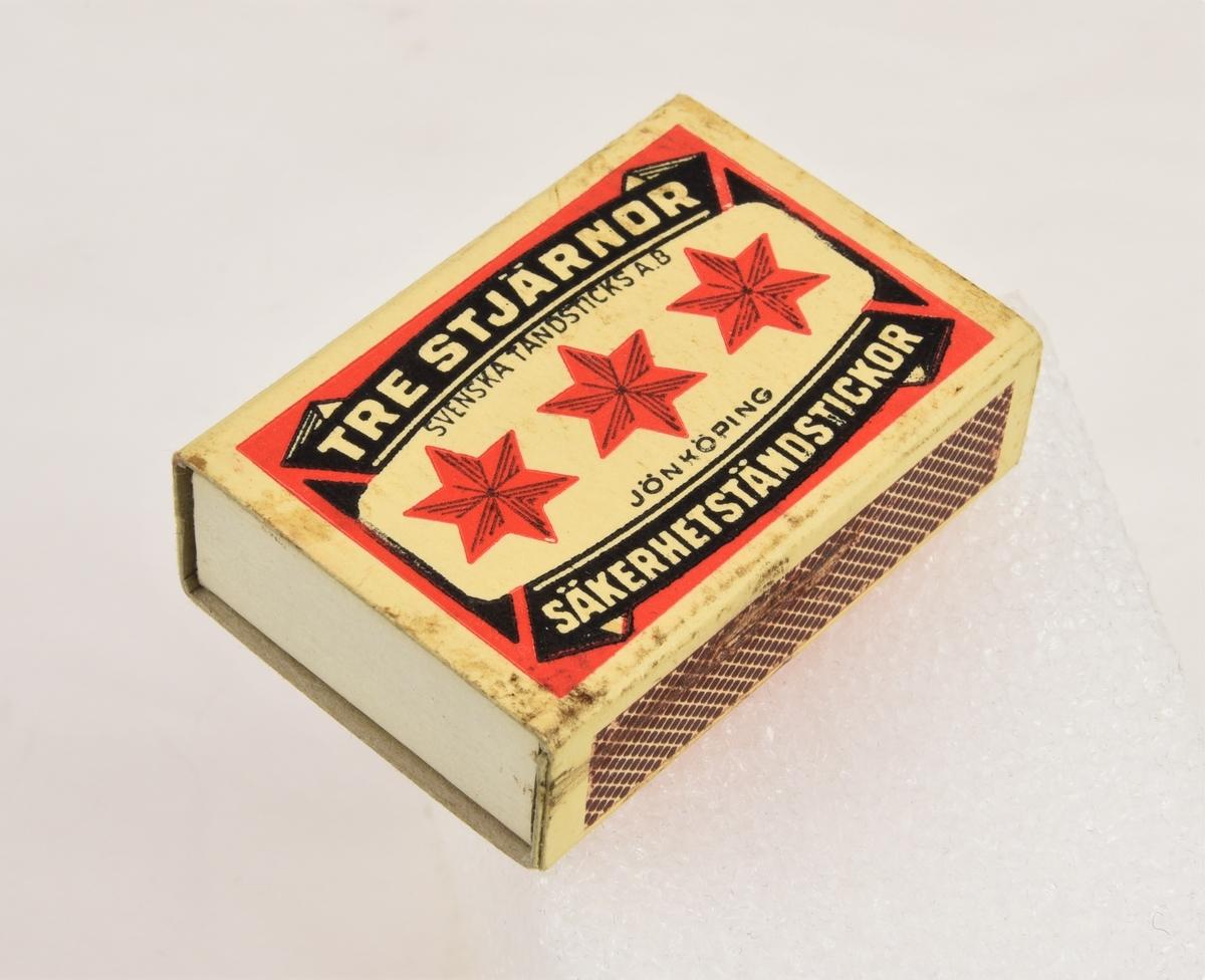 En tändsticksask som innehåller 41 stycken säkerhetständstickor.  Asken är av varumärket Tre stjärnor och pryds med tre stycken röda stjärnor mot en gul bakgrund som omges av dekorativa detaljer i röd och svart färg. Det finns ett plån på vardera sida av tändsticksasken. Askens baksida är röd.  Det finns skrapmärken på båda plånen.