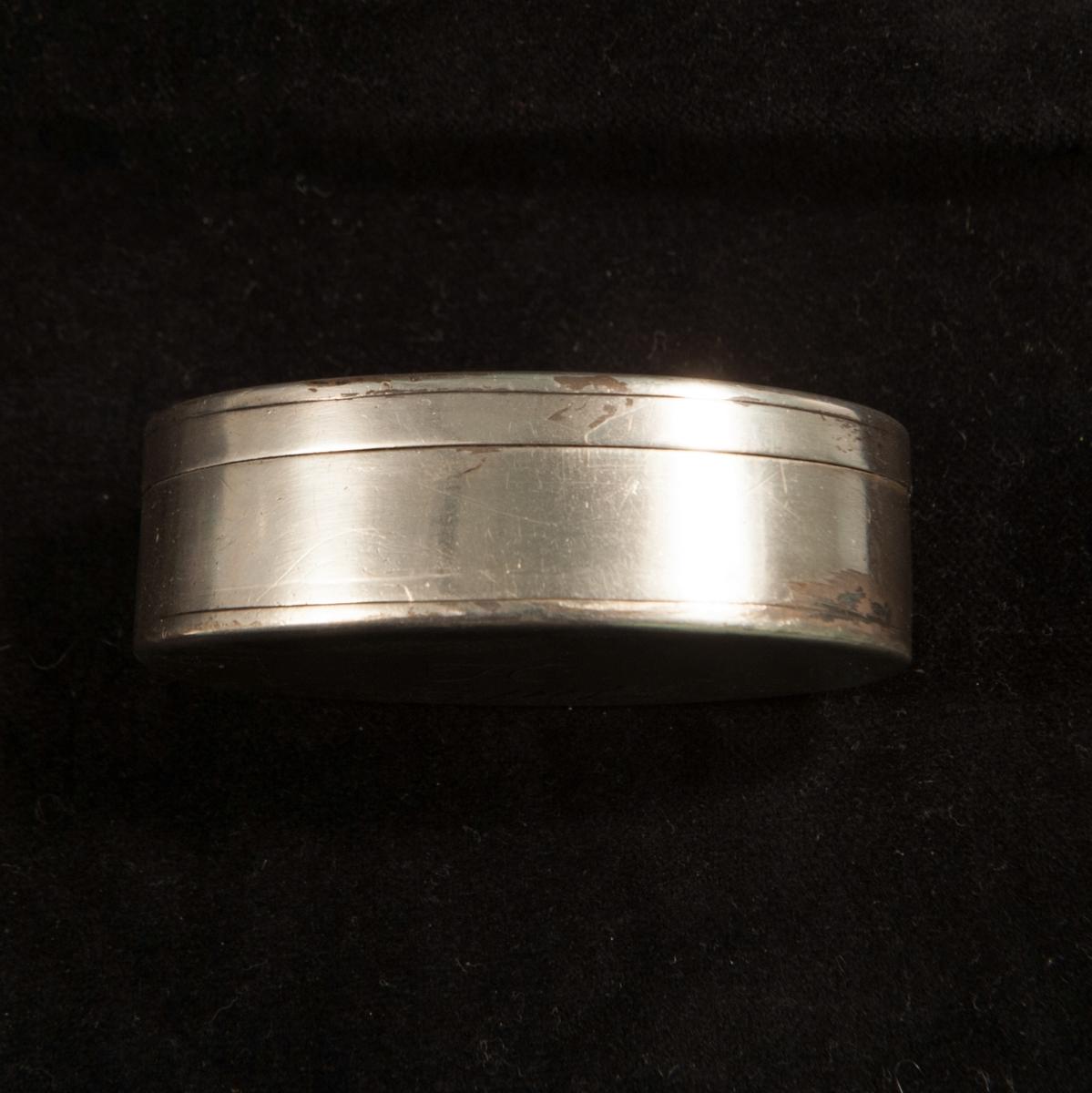 """En oval dosa av silver. Slät modell med randdekor. I botten graverade ägarinitialer i spegel monogram: """"JH """". Invändigt förgylld. Stämplad invändigt i botten."""