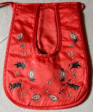 Kjolsäck i rött siden med kedjestygnsbroderi. Hedemoramönster. Baksida av rött bomullstyg + foder av samma tyg. Ett 103 cm långt röttbomullsband fäst på höger sida. En langeterad ögla i vänster sida. Mycket skadat broderi.