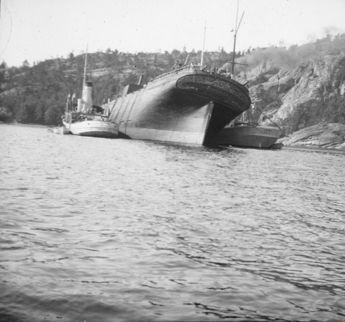 Ukjent havarert seilskip, flankert av to mindre dampskip. Seilskipet er nedrigget, og ligger ved land, kystlandskap.