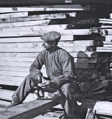 Gammelt foto av mann som spiser sittende ved en stabel sagvirke.. Foto/Photo