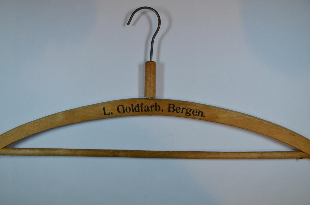 """Kleshenger i tre (med metall henger) fra Leopold Goldfarbs konfeksjonsbutikk i Bergen. Påskrift: """"L. Goldfarb, Bergen"""", på den ene siden, og """" Dresser & Frakker"""" på den andre."""