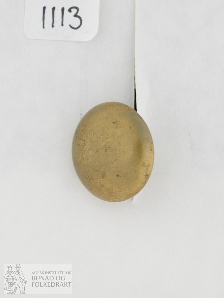 Knapp i massiv messing. Kuva form. Påstøypt krok på baksida. Knappen er sydd fast til ein skinnlapp saman med 8 andre knappar.