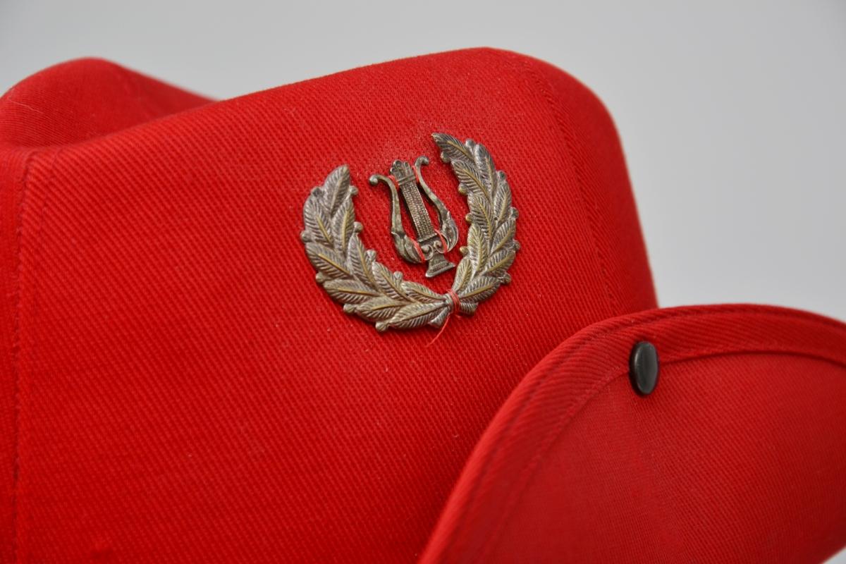 Rød uniformshatt med snor. Bremmen er festet til pullen.