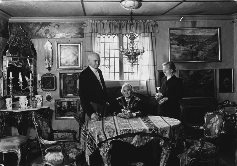 Otto, Tilla og Gundhild Bakke, deres tjenestepike, avbildet i Tillas stue i hovedhuset for Magasinet for Alle i 1962. Bordet og stolene i stuen er franske, mens lampen over spisebordet er av meronaglass fra Venezia, kjøpt i Firenze. (Foto/Photo)