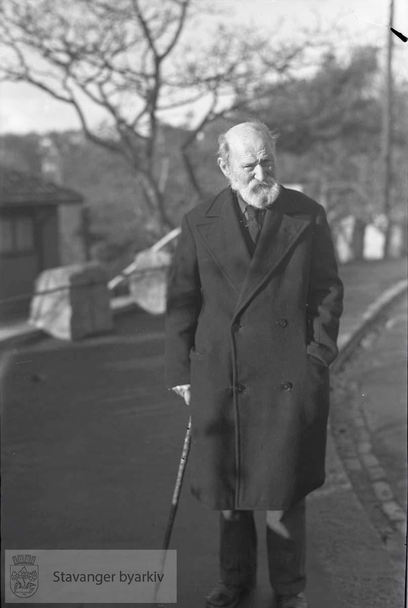Eldre mann med stokk går langs veien