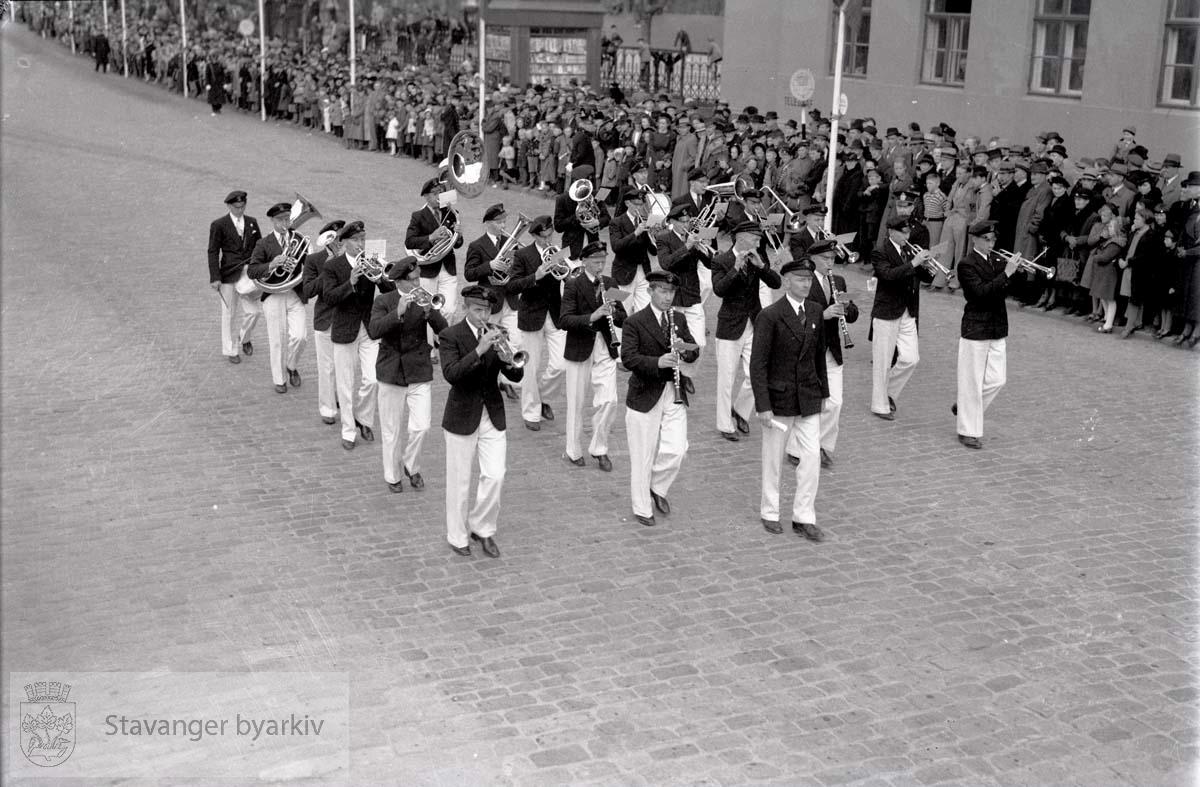 Musikkorps marsjerer i gaten ved posthuset