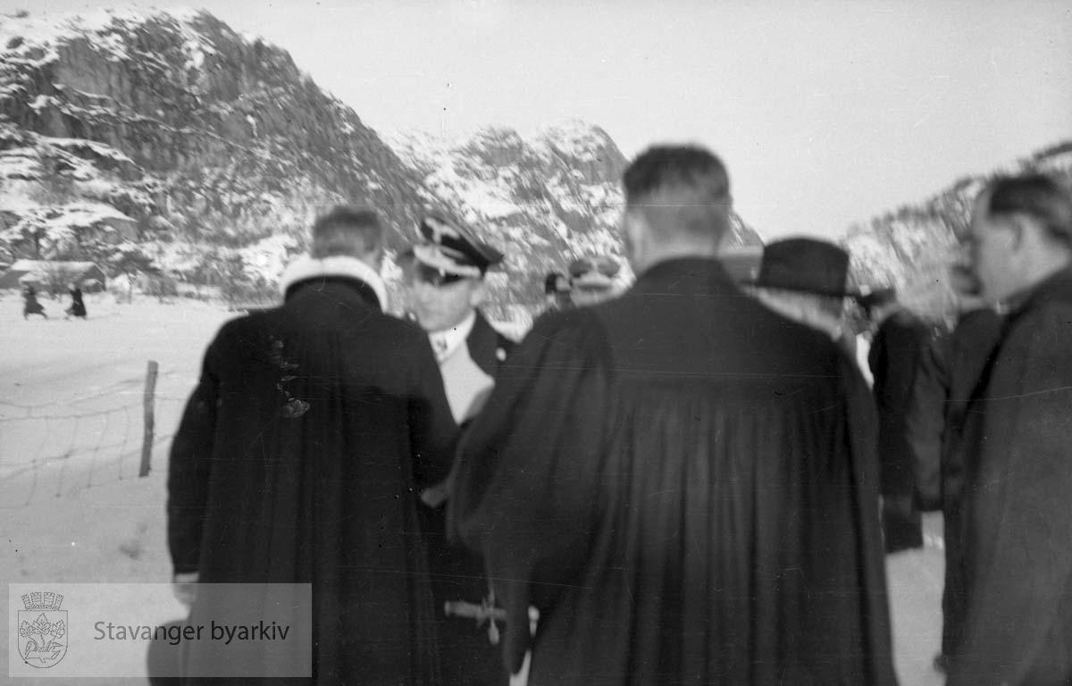Fra Altmark-affæren i Jøssingfjord februar 1940..Vi ser ryggen til presten. ..14. februar 1940 kom det tyske hjelpefartøyet «Altmark» inn på norsk sjøterritorium utenfor Fosenhalvøya på hjemvei til Tyskland. Altmark hadde ca. 300 britiske krigsfanger om bord, og det fikk lov til å passere gjennom norsk territorialfarvann, eskortert av en norsk torpedobåt...Altmark ble oppdaget av et britisk fly samme dag, og britene tok opp jakten på skipet. Den britiske jageren «Cossack» avskar om formiddagen 16. februar Altmark og forsøkte å stoppe den. Altmark søkte tilflukt i Jøssingfjorden i Rogaland, beskyttet av den norske torpedobåten i fjordmunningen. Samme natt gikk Cossack inn i Jøssingfjorden og bordet Altmark, mot protest fra den norske torpedobåten...Det utspant seg en kort kamp, og seks tyskere ble drept og flere såret. Cossack befridde de britiske fangene og stakk til sjøs..