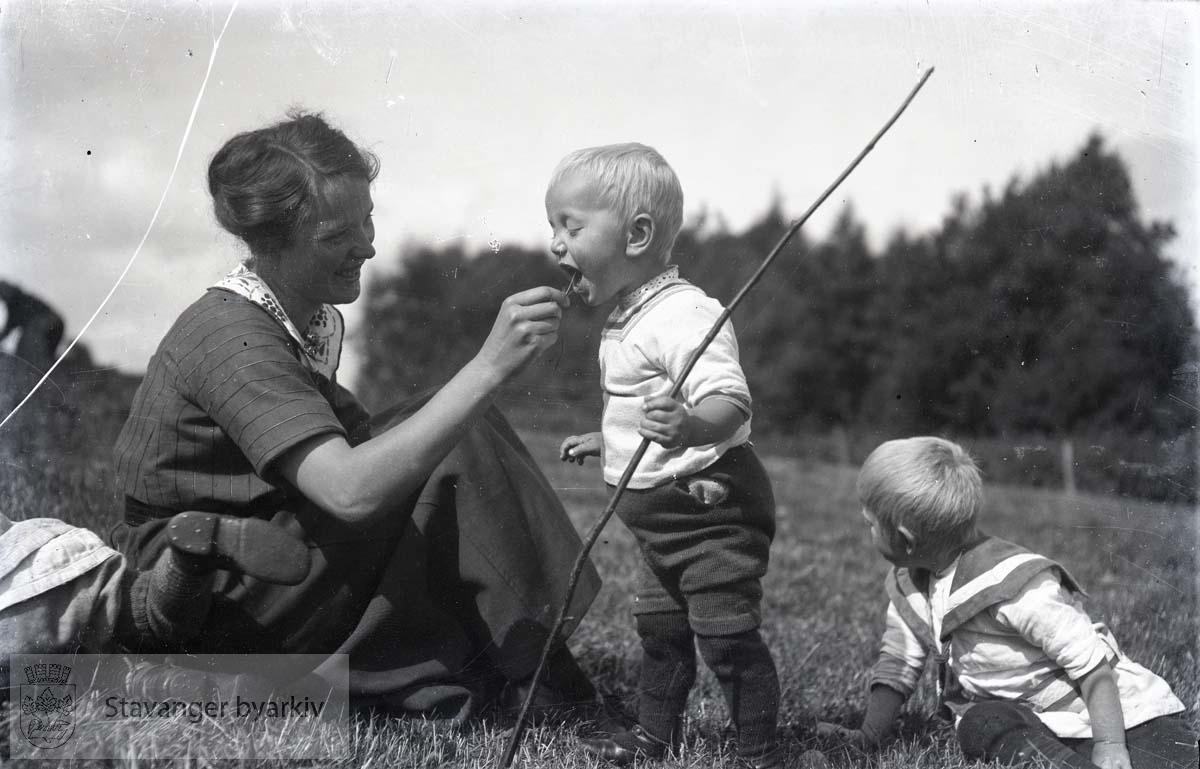 Kvinne og to barn i gresset
