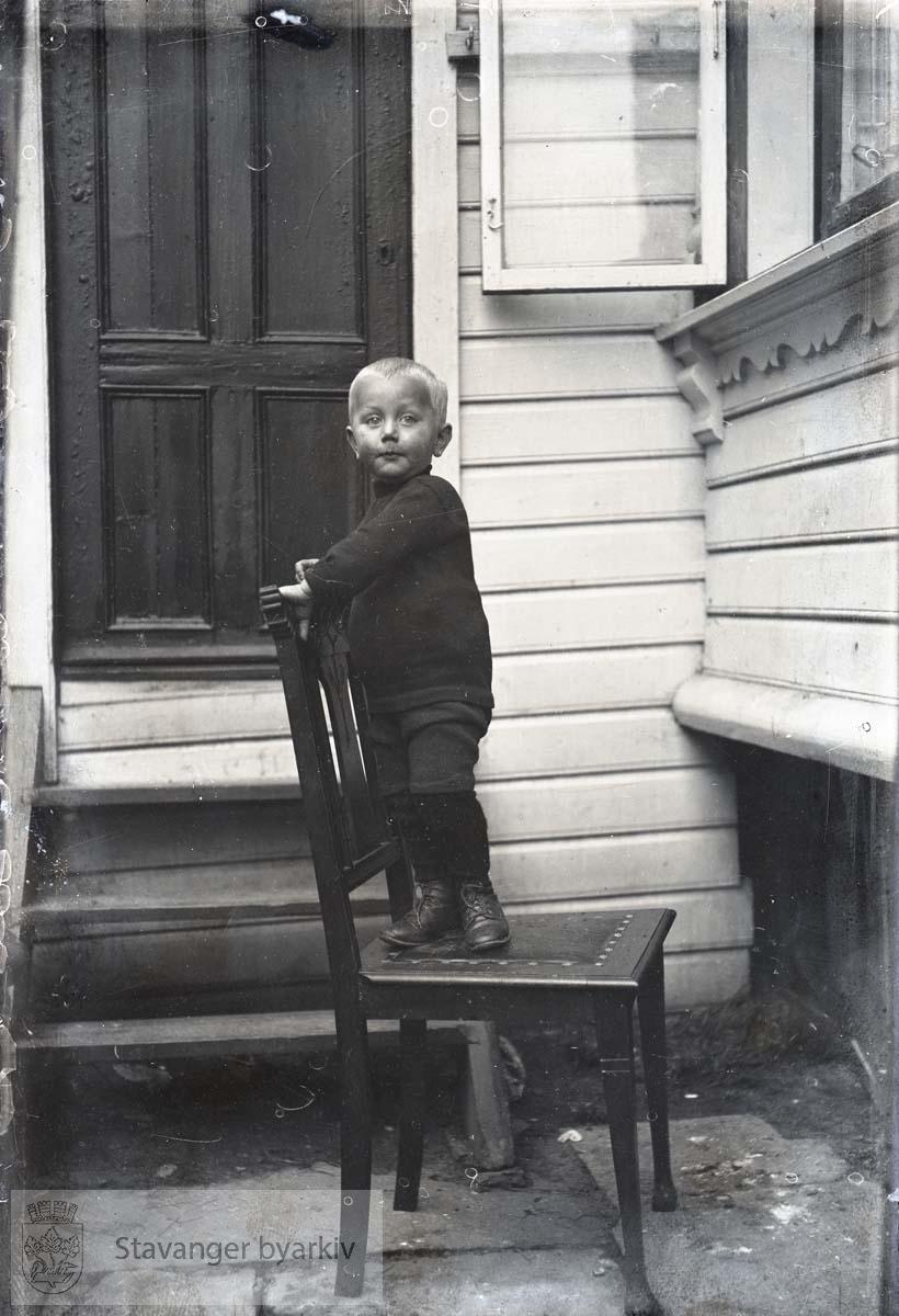 Gutt på stol utenfor huset