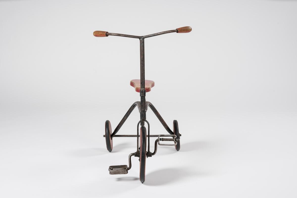 Form: Ramme av hulrør, forhjul med pedaler, flatt, innsvinget sete.