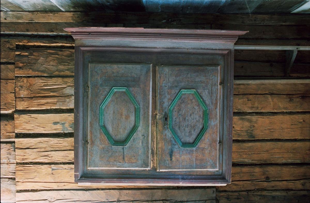 Överdel till skåp, av barrträ, ådermålad i brunt. Rakt profilerat utskjutande krön, två dörrar med 8-kantiga speglar med gröna lister, nyckelskyltar av järn. Sidostycken med spegelfack.