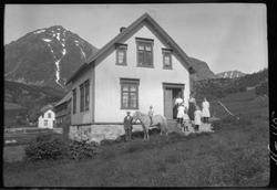 Våningshus med personer og en hest stående foran.