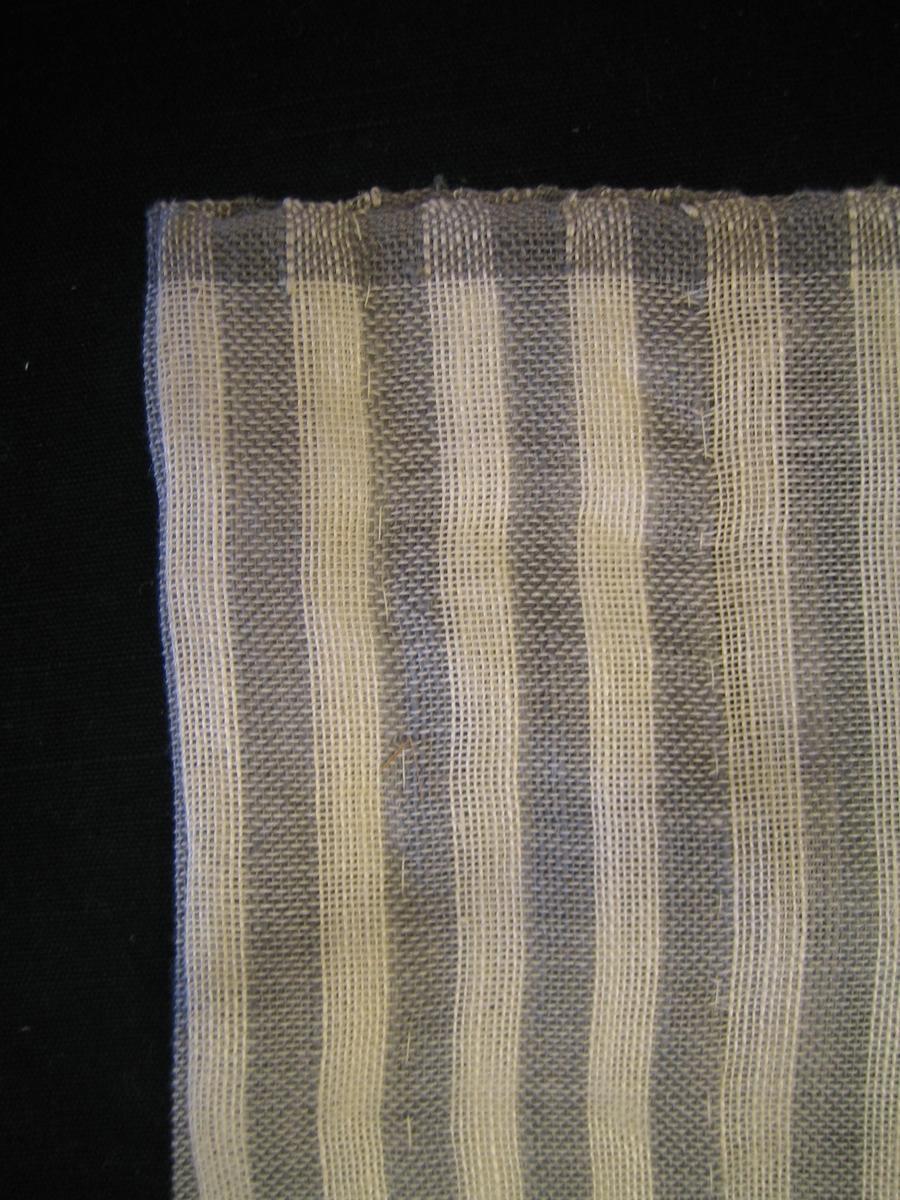 """Gardin i vitt och grått randig på tvären, väv i tuskaft med 8 mm breda ränder i vitt och grått. Gardinen är vävd i bomull i varp och lin i inslag. Stadkanterna är varpade i grått 10 mm. Komponerad Ann-Mari Nilsson. En lapp är fastsatt med texten: """"Block"""" Bredd 90 cm. Bomull, lin, Material 35:-/m"""" på ena sidan och: """"SKARABORGS LÄNS HEMSLÖJDSFÖRENING"""" på andra sidan."""