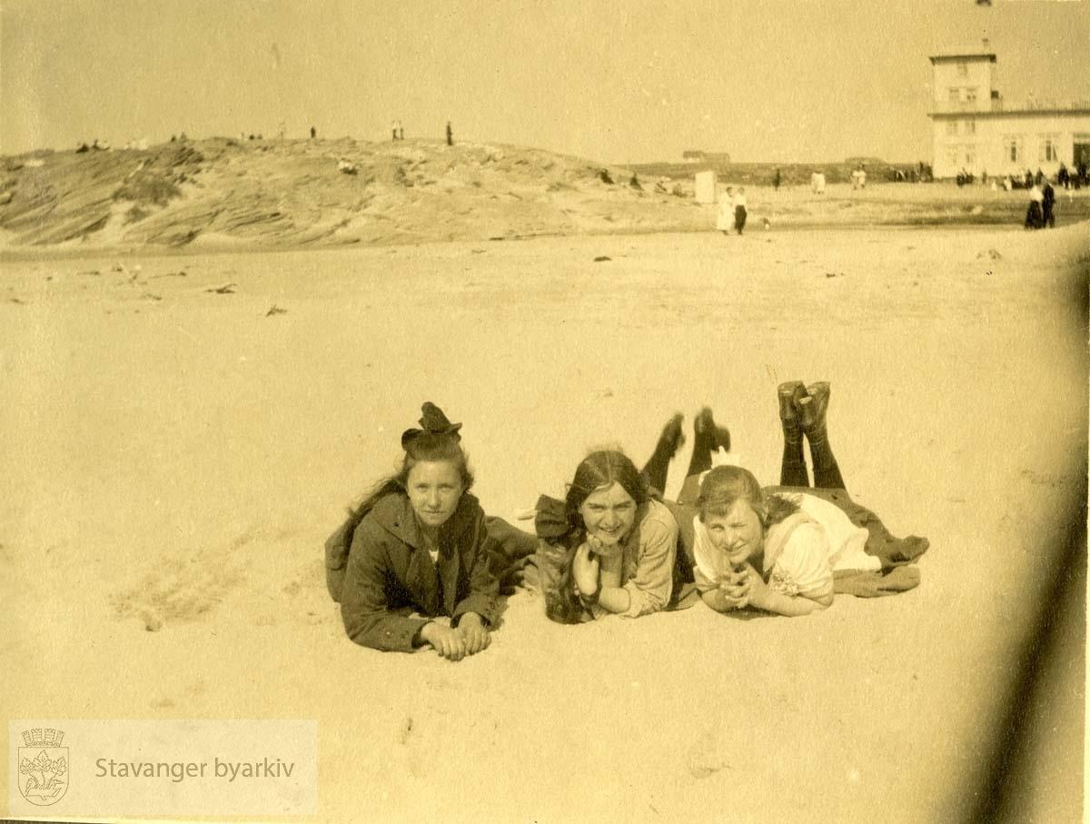 Tre damer ligger på stranden.Sola Strand Hotel i bakgrunnen