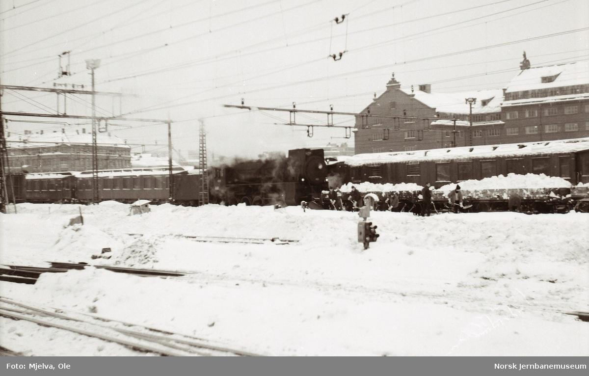 Damplokomotiv type 31b nr. 451 med godsvogner litra N2 lastet med snø på Oslo Østbanestasjon. Mannskaper spar sne opp i vognene med håndmakt.