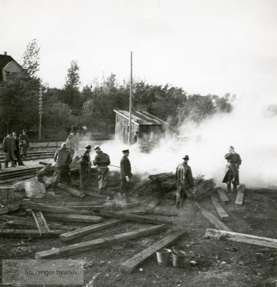 Brannområdet med brannmenn, bøtter og tilskuere.