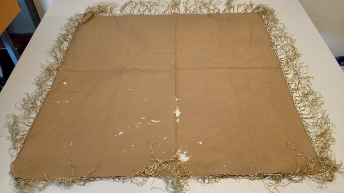 Firkanta. Ullhovudplagg med knytte silkefrynser, truleg nytta av mor til siste eigar. Plagget vart knytt under haka med enkel eller dobbel knute.   Vaska. på museet.