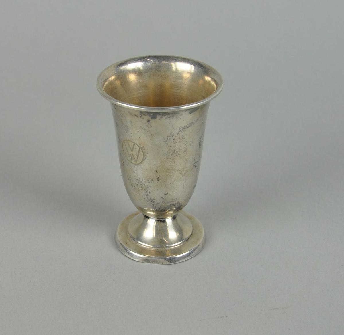 Pokal av metall, muligens sølvplett. Sylindrisk form med innsnevring nederst mot utgående sokkel. Pokalen har profilert dekor på sokkel.