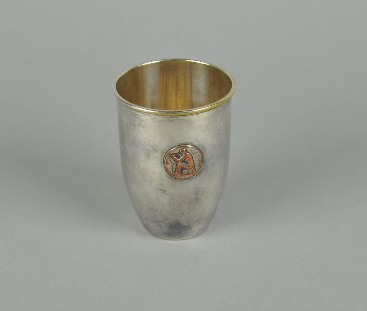 Pokal av metall, muligens sølvplett. Sylindrisk form med innsnevring mot bunnen. Det er et emblem av sittende mann med gevær på pokalen.