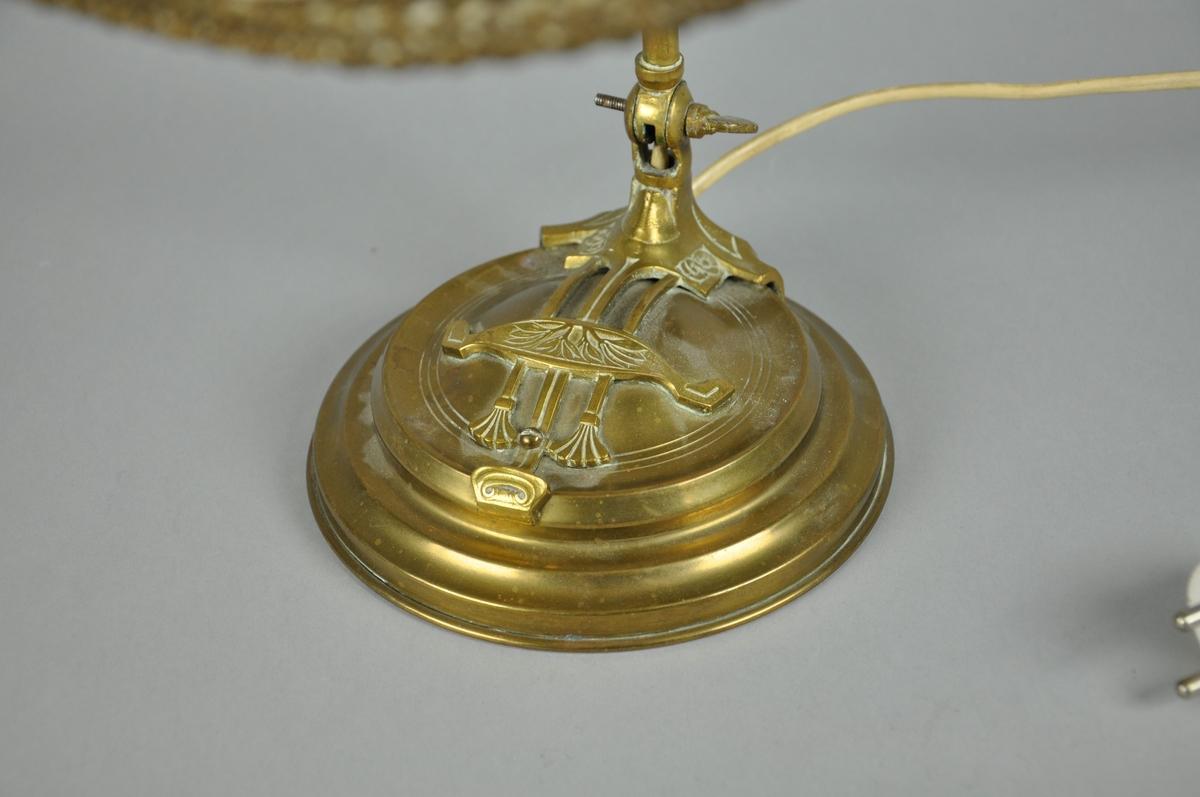 Bordlampe av messing. Lampen står på en rund, profilert sokkel. På sokkelen er det symmetrisk dekor av tre linjer som går over i to palmetter og volutt i enden. Ved overgang mellom sokkel og stang er det inngravert to blomster på hver side. Skrue for å justere stang og lampeskjerm er formet som skjell. Lampen har oval lampeskjerm med frynser og brune, kniplete border. Lampen har hvit lyspipe.