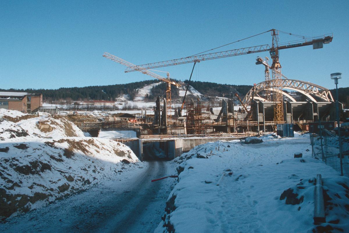 Lillehammer.  Håkons hall under bygging, oppsetting av takkonstruksjonen.  Sett mot øst.  Daværende Mesna videregående skole til venstre.