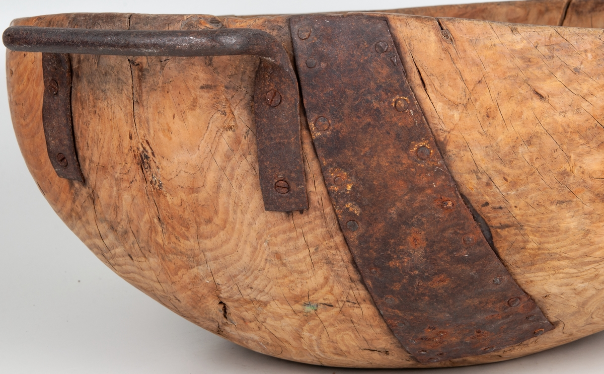 Mjölkskål, knotskål. Diam. 50 cm, höjd 22 cm. Av trä, svarvad, med järnhandtag. Lagat med järnbeslag.