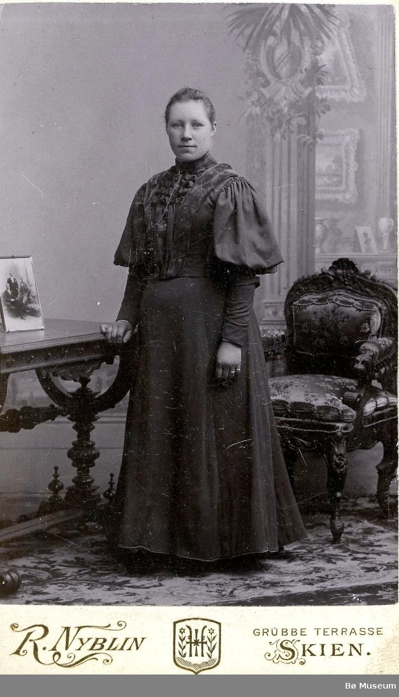 Atelierfoto av ei kvinne som står ved eit bord.