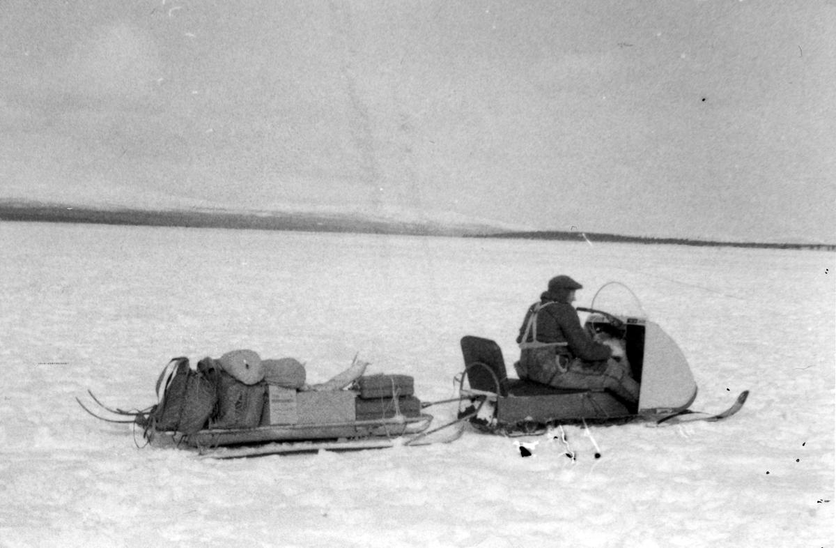 Mann på snøskuter med kjelke