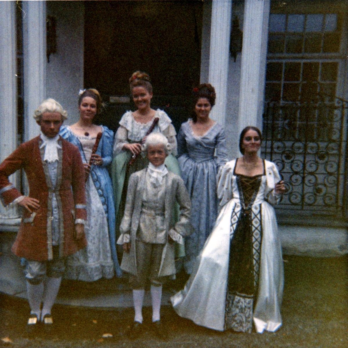 Bilde av en gruppe unge artister ikledd historiske kostymer på trappen til direktørboligen, tatt i forbindelse med en opptreden på museet. Ytterst til høyre står Ruth Wærdal, tidligere assistent ved museet.