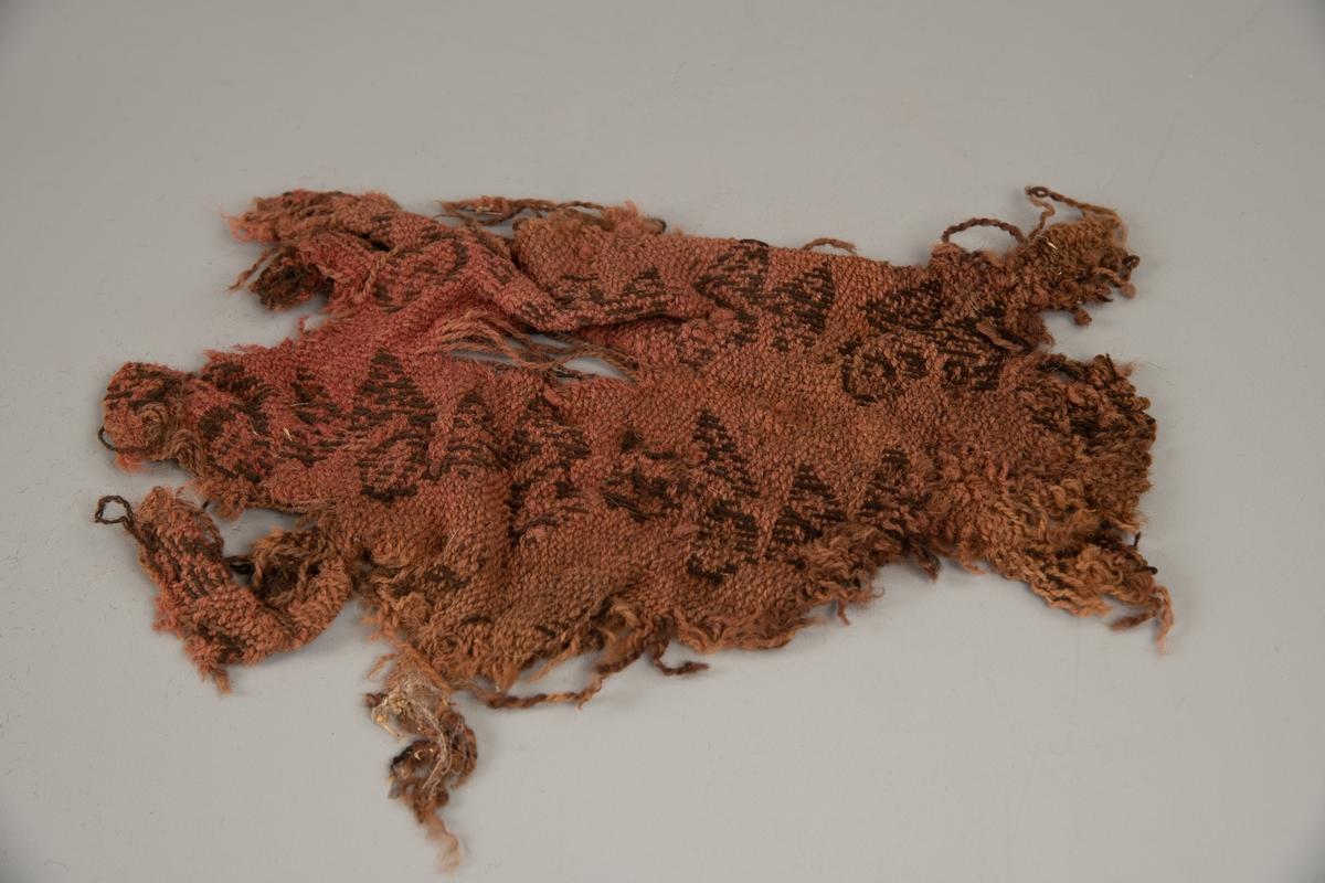 Fragment av dobbeltvevd stoff, svartbrunt mønster på  rosa bunn.  Sterkt frynset og ujevnt i kanten,  hullet.