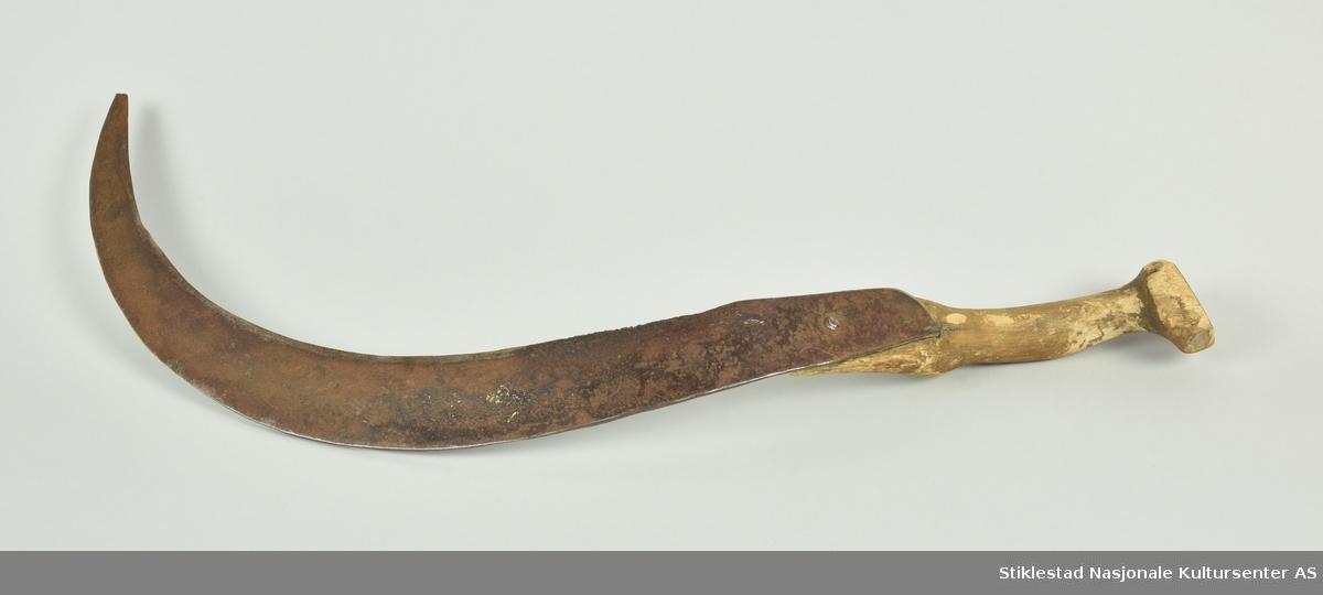 Halvmåneformet blad av jern, festet på ett skaft av naturvokst bjørk (grein). Bladet er festet til skaftet med en jernnagle, samt en tange som går gjennom ett hull i skaftet, er bøyd og banket fast til treet på motsatt side. Skaftet har buet form og teljet til for ett godt grep. Skaftet har halvmåneformet tverrsnitt ved bladfeste. Skaftknopp er sprukket. Bladet er merket AB